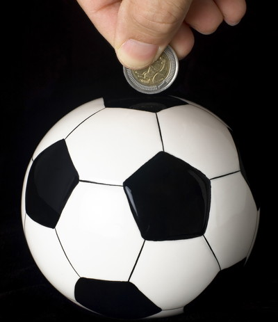 putting money in a football shaped piggy bank