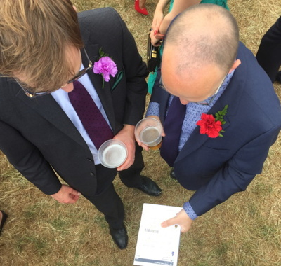 race card couple of guys reading one at a horse meeting